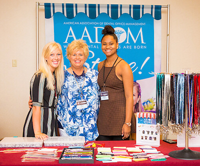 Three women standing in front of a AADOM sign and behind a desk