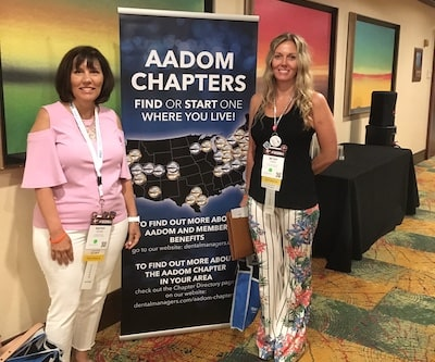 Kathy and Betsy standing either side of a large banner promoting AADOM